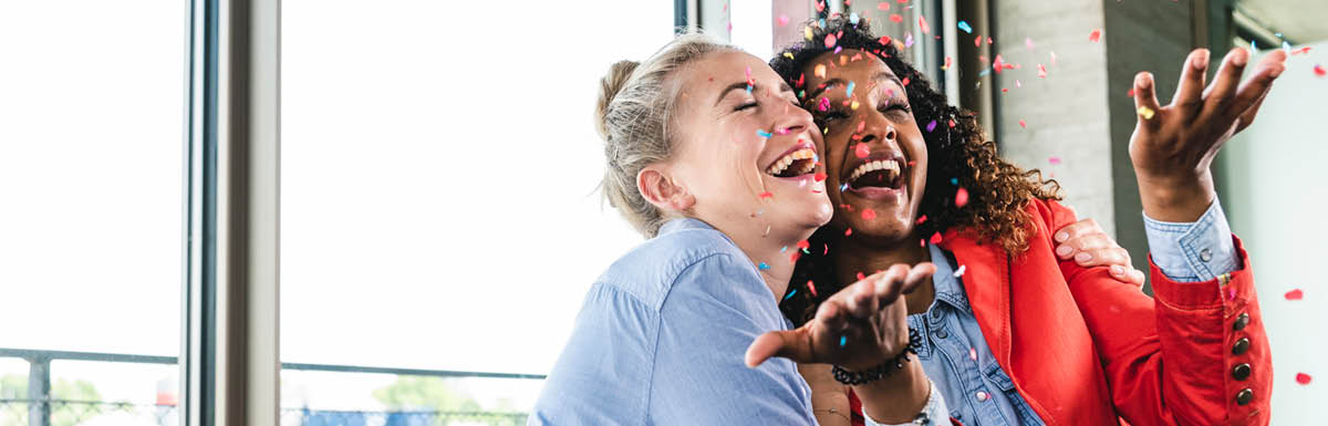 Two woman smiling with confetti